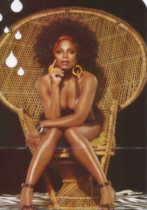 Janet with an afro sitting in an wicker chair leaning forward so we can see her cleavage